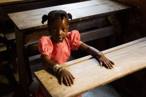 A girl sits at her desk at school in Guinea. Her school has just reopened after the Ebola crisis and Unicef is supporting teachers to implement safety measures against the disease. Photo: Unicef/Guinea 2015/Perret