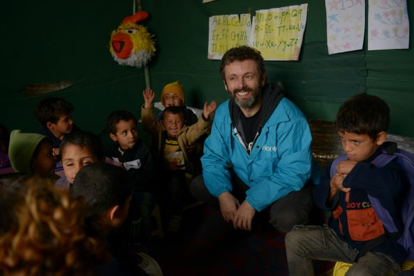 Michael Sheen meets Syrian refugee children in Lebanon as they receive their first winter supplies from Unicef - including boots, gloves and warm clothing. Photo: Unicef/2013/Brooks