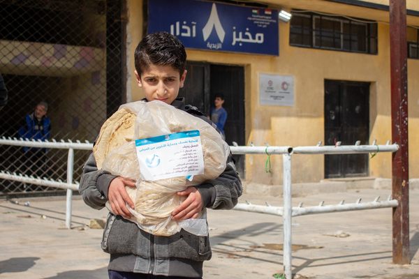 On 2 April 2020, Mohammad, 11, holds a bread bag containing messages raising awareness on issues around the 2019 novel coronavirus, in the al-Zebdieh neighbourhood of Aleppo, Syrian Arab Republic.